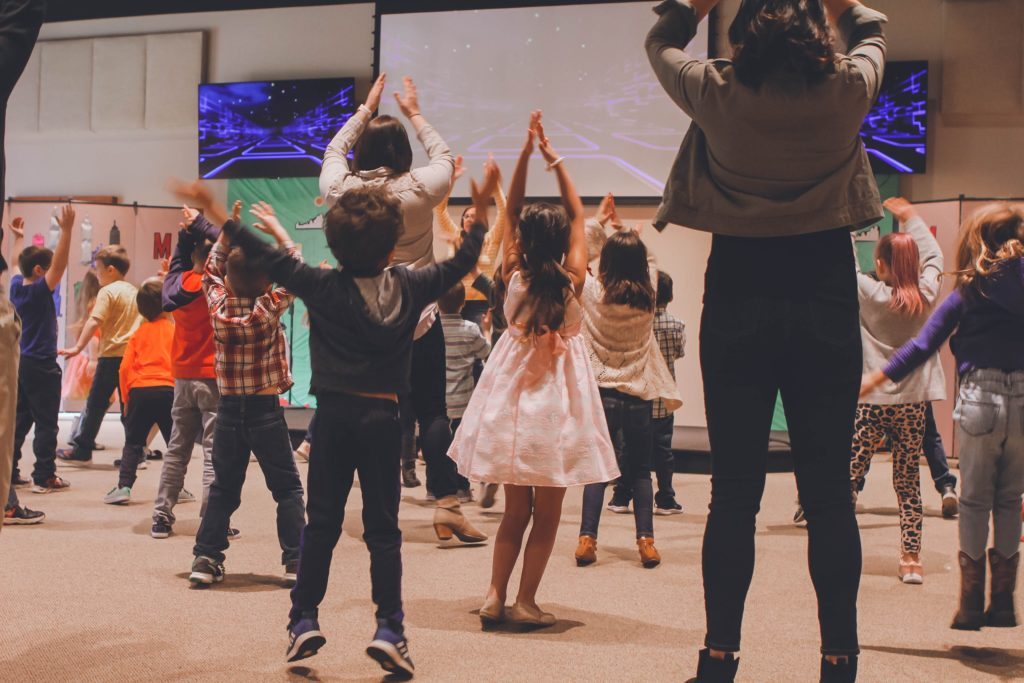 Kids in a worship group jumping and dancing together